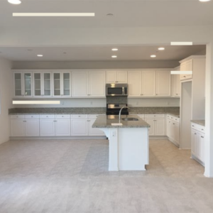 View of new kitchen with white cabinets and grey color scheme to accent stainless steel appliances.